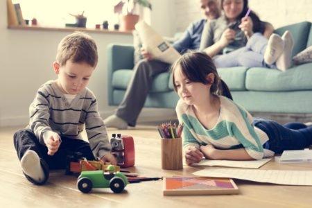 irmãos brincam no chão enquanto pais estão no sofá